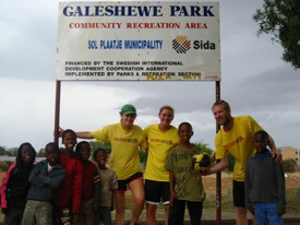 Kristen Fladseth, Anna Barrett, and Peter Glidden pose with local Galeshewe children during the 2009 Galeshewe Dribble-A-Thon.