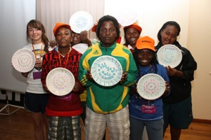Girls from Namibia, South Africa, and the US hold up plates that they decorated during a nightime art activity.